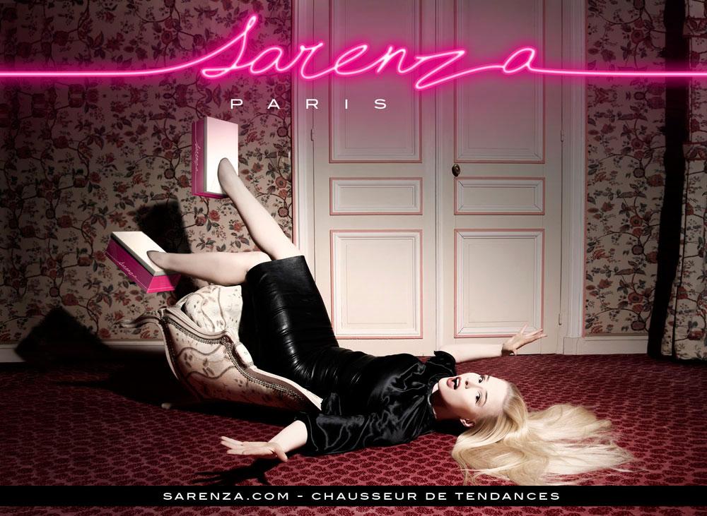 Feiernde hübsche Frau, liegend auf dem Boden, mit den Schuhkartons anstatt Schuhe in der Werbekampagne des Online-Schuhhändlers Sarenza 2012.